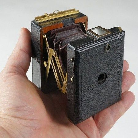 Antique Camera: Vest Pocket Format Monroe Camera, c.1898. This is a tiny strut-style, bellows folding camera made by the Monroe Camera Company of Rochester, NY. It fits easily in hand and sized just right for a vest pocket (as intended). Pictures are 2 x 2½ inch images on glass plates or sheet films.