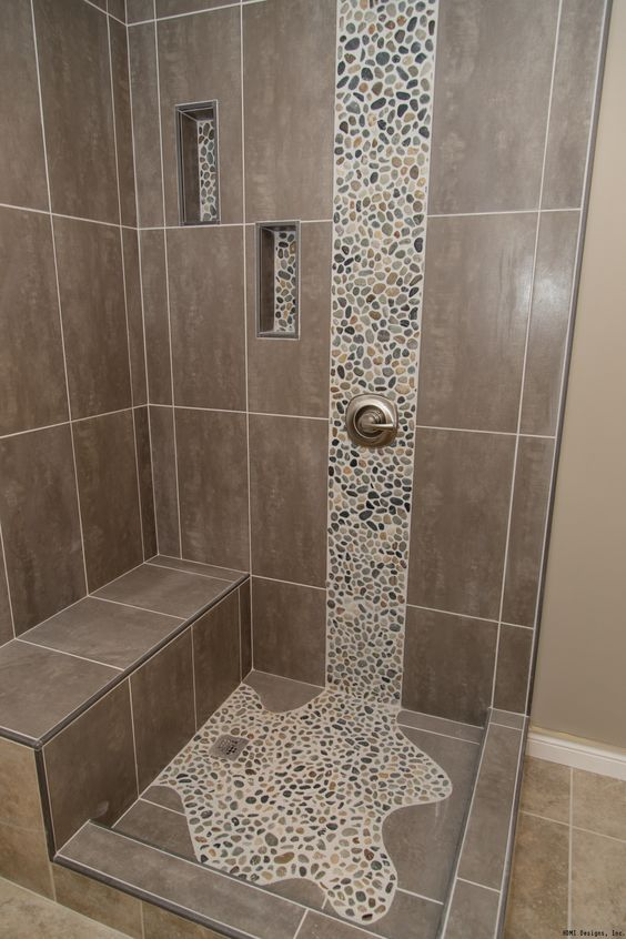 Spruce up your shower by adding pebble tile accents! Click the pin to get started on your next bathroom remodeling project.