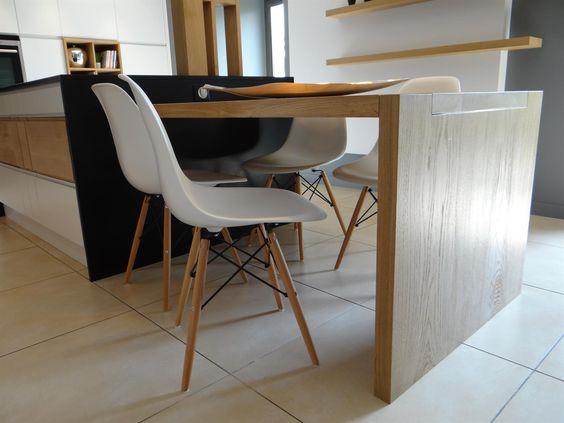 La table de cuisine en bois clair prolonge lîlot central
