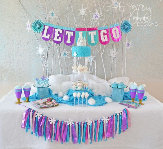 A Disney Frozen party inspired by the beautiful colors in movie. The wreath, Let it Go banner, cake, lollipops and cotton candy follow the color palette.