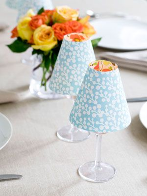 """These clever """"lamps"""" can give your table a chic, cheery feel — perfect. Gather wineglasses, scrapbook paper, LED tea lights, scissors, and double sided tape. Cut out the shades at using template; tape to secure. Print template on a piece of 8.5"""" by 11"""" paper, then cut it out. Trace the shape onto your scrapbook paper to create the shade."""