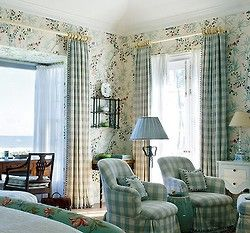 Love the mix of turquoise floral print wallpaper and turquoise buffalo check upholstery and drapes in this sitting area in a master bedroom.