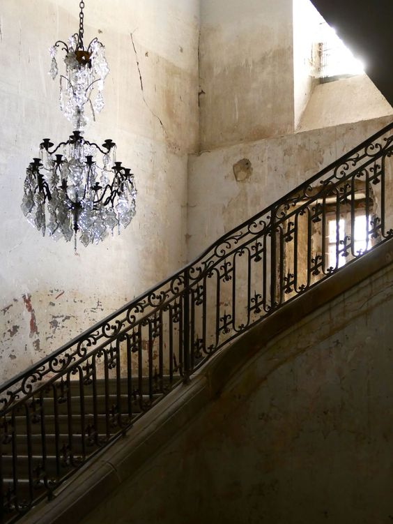 Crumbling staircase in Chateau Gudanes with crystal chandelier and decaying, weathered walls. Weathered Walls & Déshabillé Lovely. #French #chateau #staircase #chandelier #walls #weathered #oldworld