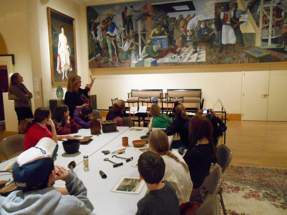 Fifth grade students handle authentic historic objects while learning about connections between American history and art during their Picturing America field trip tour.