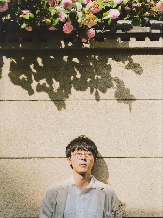 白いカーディガンを着て塀の前に立っている高橋一生の画像