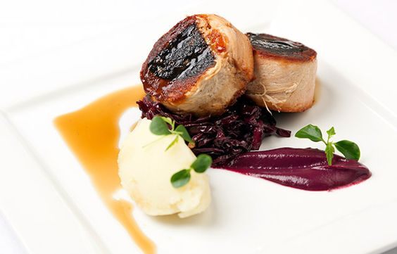 Confit belly of pork stuffed with black pudding with braised red cabbage, mash and cider jus