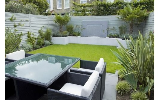 JMK says:- I like his neat simple layout and the glass table that reflects the light.Painting the walls white lightens up the space. Grass looks like Astro Turf?