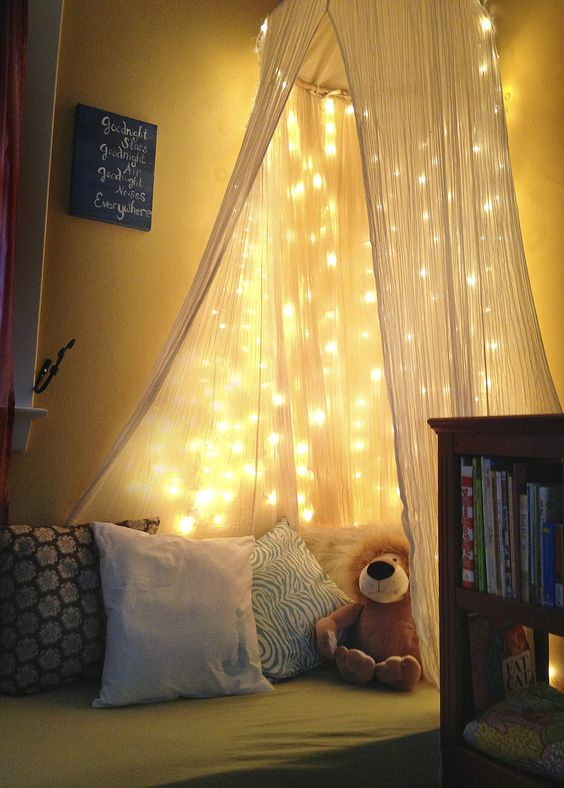 DIY toddler reading nook  -White christmas lights, old crib mattress, cotton fabric to make your own pillow cases, IKEA throw pillows, gauze canopy from World Market. Can make this for under $50.00.