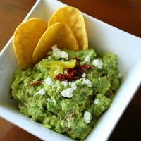 Tangy Mediterranean Guacamole:  Roughly mash 4 to 6 avocados with 2 T plain yogurt, 3 T sliced pepperoncini peppers plus 1/4 cup of the brine from the jar.  Add 1/8 tsp EA garlic powder, and black pepper, 1/4 tsp salt, 1/3 cup sliced oil-pack sun-dried tomatoes, and 1/2 cup goat cheese crumbles.