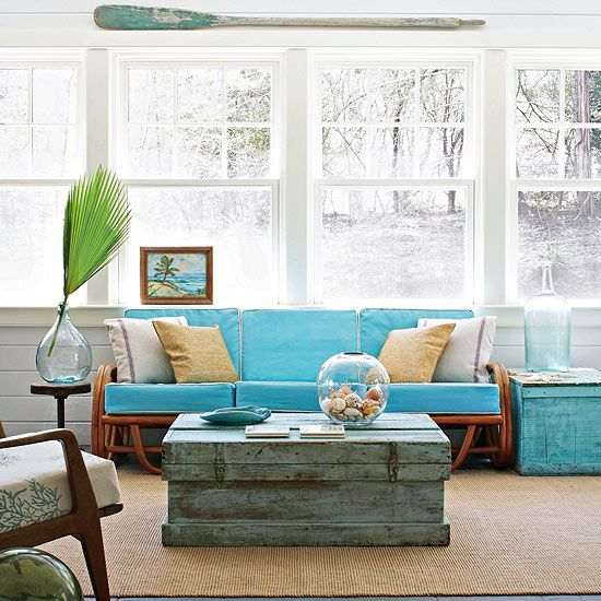 This cozy sunroom sports a classy tiki room theme. A palm frond and other tropical motifs help unify a comfortable blend of country, rattan, and mid-century modern furnishings.