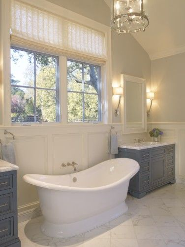 traditional bathroom with grey blue vanities and stand alone tub