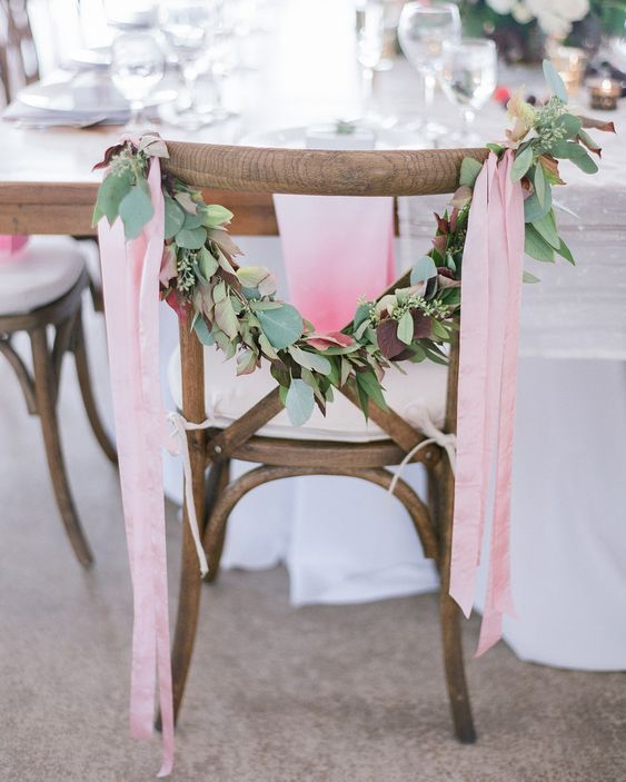 Greenery garlands with pale pink ribbons added a pop of color to an all-white tablescape.