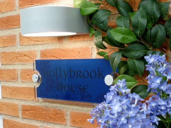 beautiful blue house name plate on brickwork with modern light and fab flowers