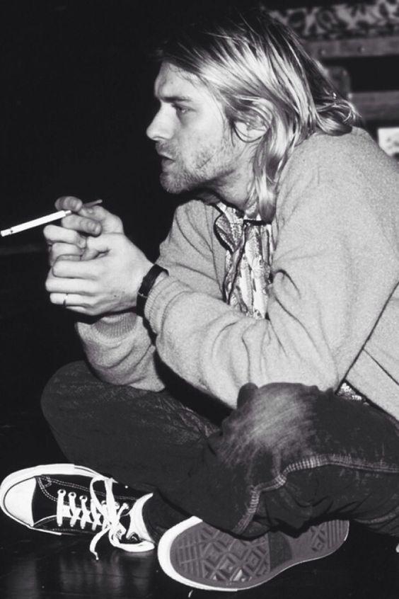 """Kurt Cobain, vocalista da banda Nirvana. Foi uma grande influência nos anos 90, não só a nível musical, mas também tornou-se um icon de estilo dessa geração, onde deu origem ao estilo """"grounge"""". Ainda hoje em dia é considerado uma referência de estilo, notado em colecções de conhecidos estilistas, como Marc Jacobs (1992 para Perry Ellis) e Yves Saint Lourent (Outono/Inverno 2013)."""