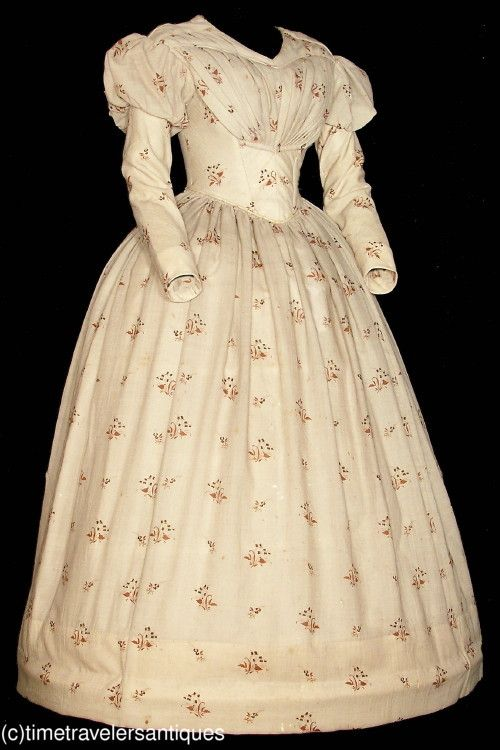 Late 1830's floral printed cream silk challis one piece gown that is a wonderful example of a transitional style. The bodice is lined ans stayed, with a fan pleated front, piped at all the seams, with fashionable slender capped sleeves, a two part back with a blind hook and eye closure, a cartridge pleated waistband, and an unlined skirt with a deep turned and faced hem.