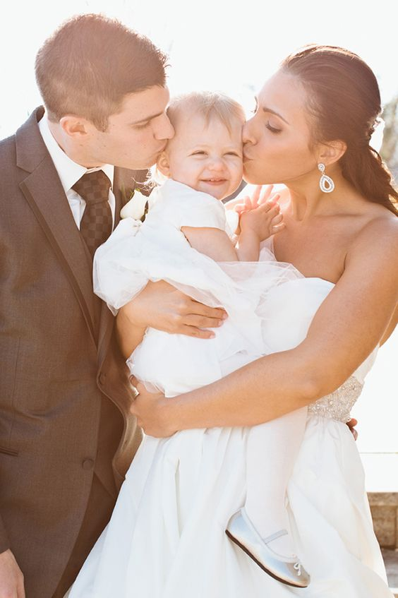 Bride and groom kissing the flower girl, their daughter | Photo by Erin McGinn #adorable #flowergirl