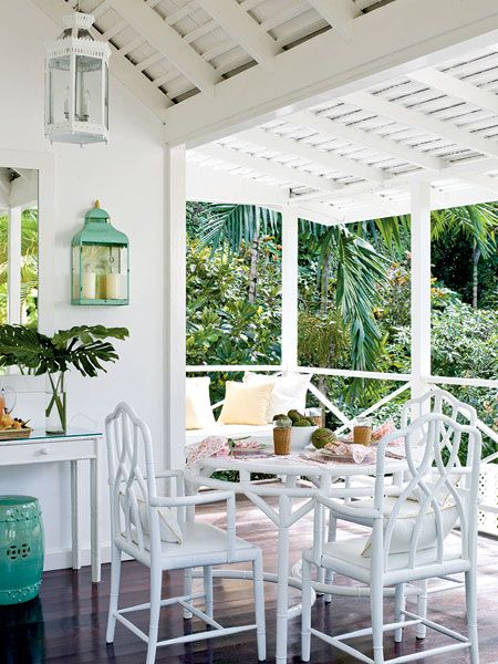 Bamboo furniture creates a retro-chic dining porch in this coastal home. Update a vintage dining set with a fresh coat of white paint, and pick one accent color, such as sea green, shown here. (Photo: J. Savage Gibson)-sunroom