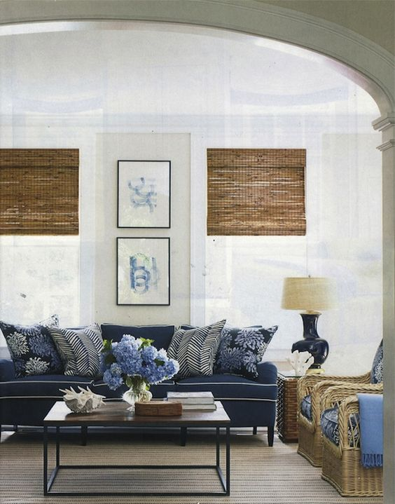 Elegant beachy cottage living room design with soft sand walls paint color, bamboo roman shades, blue cushion sofa with white piping, brickmaker's coffee table, wicker chairs with blue cushions and glossy blue gord lamp. (Lynn Morgan Design)