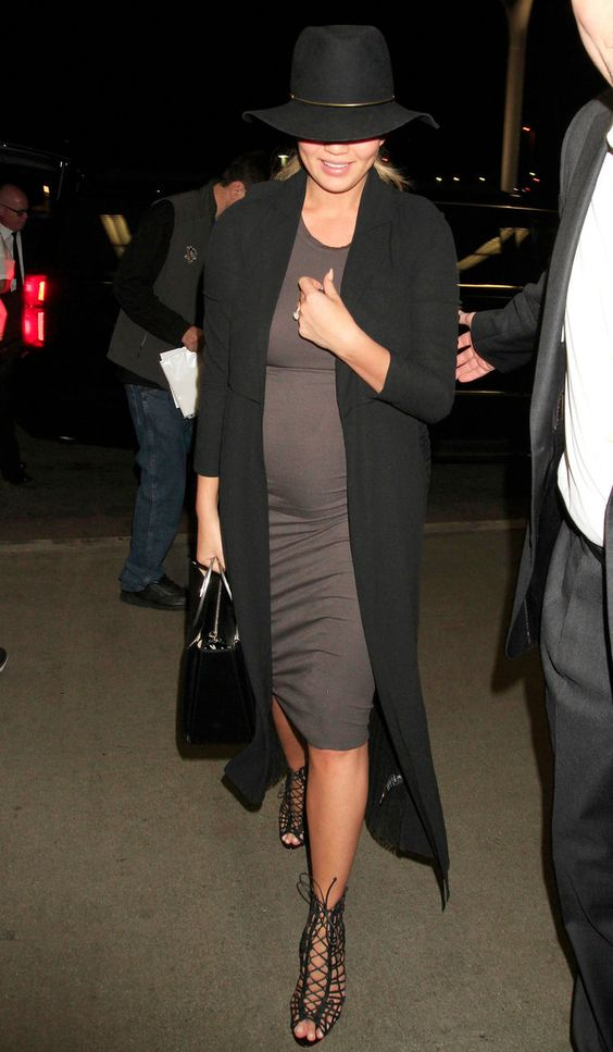 Chrissy Teigen arrives at the airport in a tight gray dress and black duster coat.