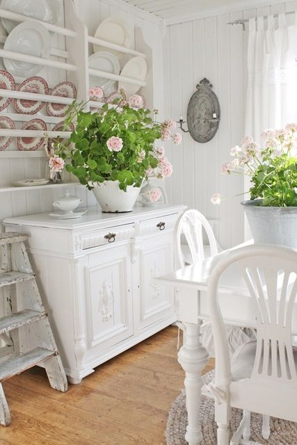 Fresh,  white cottage dining room -  red and white transferware plates and pink geraniums add just the right touch of color.