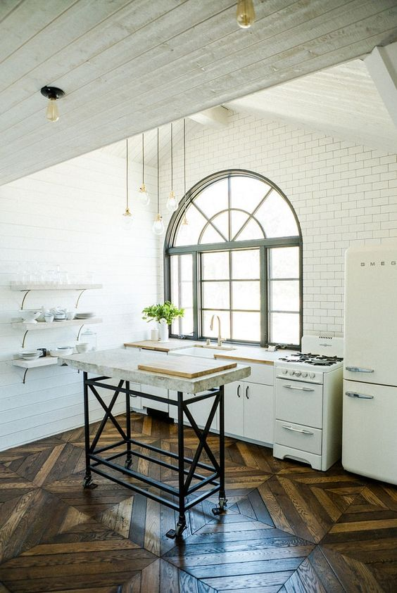 Kitchen designed by Leanne Ford with arched window, vintage stove, aerringbone wood floor, open shelving, and lofty ceiling. #minimaldecor #kitchendesign #LeanneFord