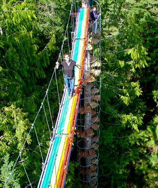 """The """"Stairway to Heaven,"""" Mount Rainier, WA, begins at the base of a fir tree and spirals to 82 feet into the sky. A rainbow-colored suspension bridge stretches 43 feet over the forest floor. It's the only way to reach the Treehouse Observatory, which provides expansive views of Mount Rainier and the Nisqually Valley. The Cedar Creek Treehouse accommodation is 50 feet up a nearby tree."""