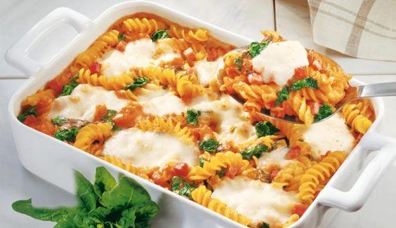 """Beim Nudelauflauf """"Tomate-Mozzarella"""" mit Spinat schmeckt das grüne Gemüse auch den Kleinen. Saftige Tomaten und würzige Schinkenwürfel machen das Gericht zu einem Favoriten für die ganze Familie."""
