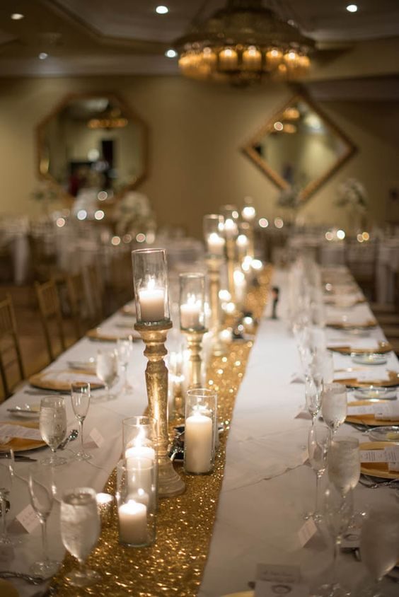 Candles on gold candle stands and gold glitter table ...
