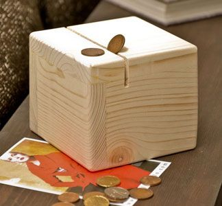 A solid wood hand made Money-box.