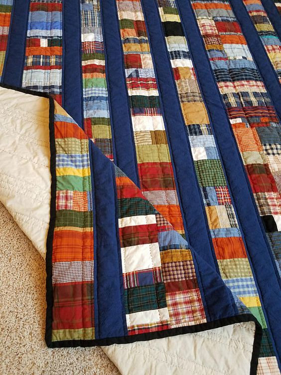 This bright, soft quilt is made from a variety of plaid and solid fabrics with solid blue sashing; many of the plaid fabrics are from recycled shirts. The fabrics are 100% cotton, the batting is polyester and the backing is 100% cotton muslin. The blue sashing fabric is homespun,