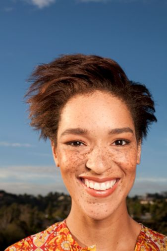 A beautiful redhead woman with freckles of African-American ethnicity.