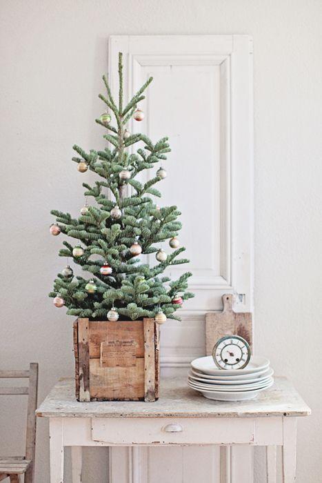 Sapin dans une caisse en bois décoré de quelques boules de Noël