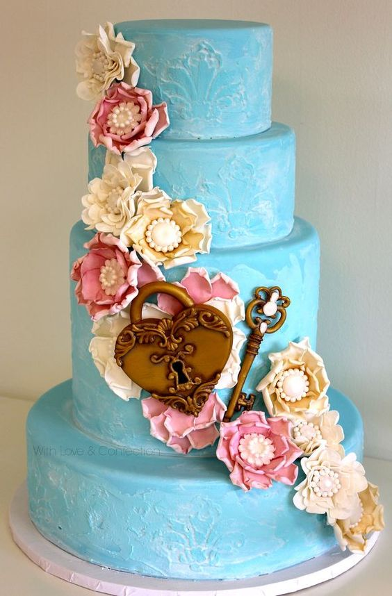 "Key to My Heart Wedding Cake by Veronica Arthur.   All decorations are hand sculpted with gumpaste. Gumpaste flowers with hand made isomalt brooches. Gumpaste lock and key.Textured and stenciled with royal icing then ""whitewashed"" with edible paint."