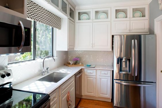 Making use of any available natural light in a small kitchen is key— a well-placed, glossy backsplash catches the window light, reflecting it throughout the space.