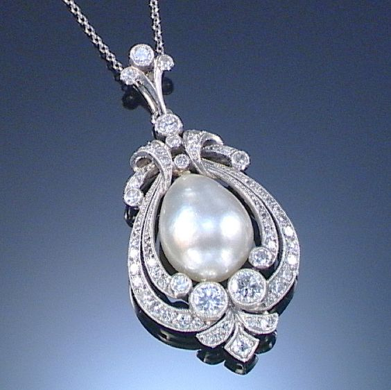 PEARL AND DIAMOND PENDANT, EARLY 20TH CENTURY.  Set at the centre with a baroque pearl, encased by open work radiating surrounds millegrain-set with brilliant- and single-cut diamonds, on a fine chain, length approximately 410mm.