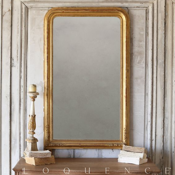 Eloquence® Antique Mirror Beautiful antique Louis Phillipe Mirror in weathered blonde gilt finish. Lovely hand-carved patterning around borders, and etched floral and leaf details on frame. Original mirror glass with glittering snowflake-like marks in the reflection.