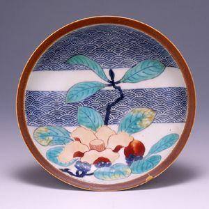 色絵銹釉椿文皿/ 見込みに一輪の椿が描かれた、堂々とした5寸皿である。椿の花は、日本人には特に馴染みが深く、鍋島でも数多く描かれているが、椿のどの品種を図案化したものかは定かでない。椿の背景には、帯状に青海波の文様が、墨はじきの技法が使われ、椿の花を引き立たせるために一役をかっている。また、皿の縁に銹釉が施されており、同形・同裏文様の縁に青磁釉が施された「染付青磁藤袴文皿」、縁に瑠璃釉が施された「色絵瑠璃釉羊歯文皿」と同時期に造られたものと思われ、鍋島の斬新なセンスを見ることが出来る。