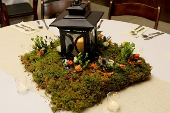 Lanterns with a moss base (would lose all those little flowers) or centerpieces of white hydrangea on mat of moss-sprinkle with blue votives