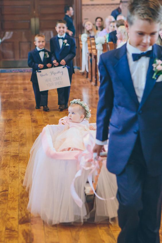 A wagon, covered in ribbon and tulle, can be the perfect way to transport one of the youngest members of the wedding party down the aisle.