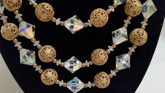 This three strand choker style necklace is in very good vintage condition. The bicone chrystal stones have a beautiful sparkle, the different facet cuts in the stones pick up an aurora brilliance.  Its a stunning retro piece from the 1960's. Measures 15 inches around neck from clasp to end of c
