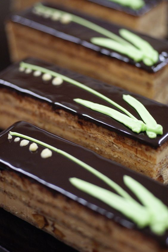 Gateau Muguet (Cake made with almond flour and flavored with Cointreau syrup, caramelized almonds, and caramel cream.) The decoration is simple but striking on the dark chocolate background. The chef says he made this cake for May 1st, when people give lily of the valley in France. [From Patisserie Plaisir]