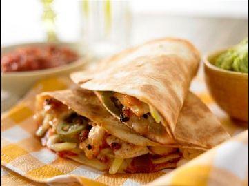 Warme Quesadillas gefüllt mit Hühnchen und Käse, verfeinert mit Tomatensalsa und nach Belieben serviert mit Guacamole Dip und Jalapeños.