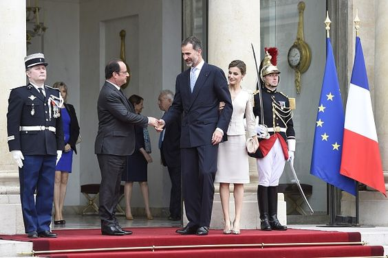 French President Francois Hollande shakes hands with King Felipe VI of Spain as his wife Queen Letizia watches while leaving the Elysee palace in...
