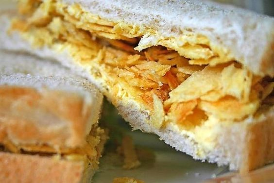 "CRISP SANDWICH A British childhood classic Take a small pile of slightly-crushed crisps (potato chips) and squish them, with raw sliced onions, between two generously buttered slices of (I quote) ""the most unhealthy white bread you can find."" Voila!"
