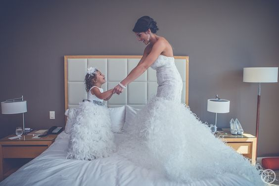 flower girl (bride's daughter) and bride jumping on bed