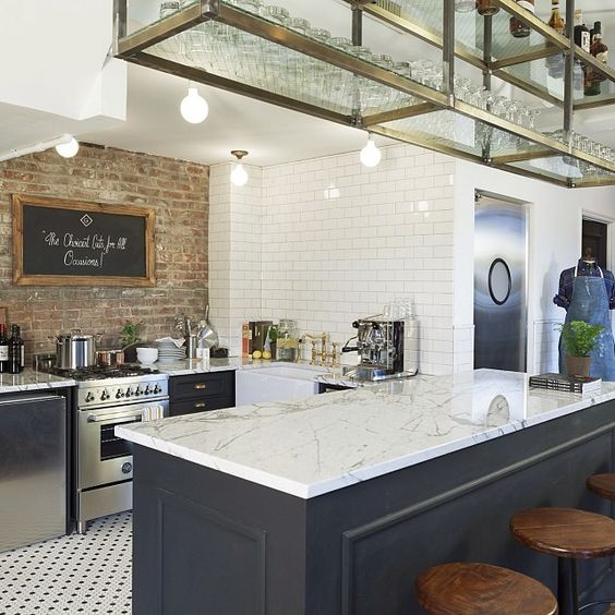 Love this kitchen. Brick wall, tile floor, open rack above for glasses. Similar to a bar great for a college brownstone.