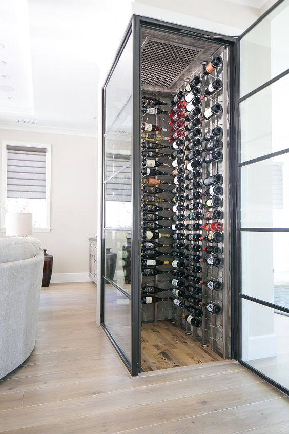 Forget the dark and dusty wine cellars we often find in basements. Today's wine cellars are all about displaying your beautiful wine collection. This glass enclosed climate controlled wine cellar keeps your wine handy while bringing some character to your home. Glass whine cellar. Living room glass wine cellar #glasswinecellar #winecellar Patterson Custom Homes. Brandon Architects, Inc.