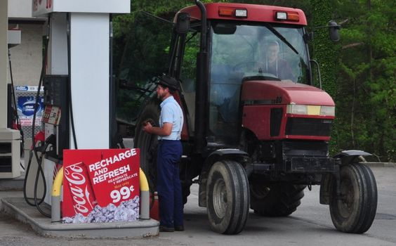 Paying at the pump, the Amish of Oakland drive big tractors into town.