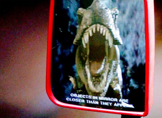 """The movie """"Jurassic Park"""", based on the novel by Michael Crichton, directed by Steven Spielberg. Seen here in the mirror of a moving jeep, a reflection of an approaching Tyrannosaurus Rex. The rear view mirror states: """"Objects in mirror are closer than they appear."""" Theatrical release June 11, 1993."""