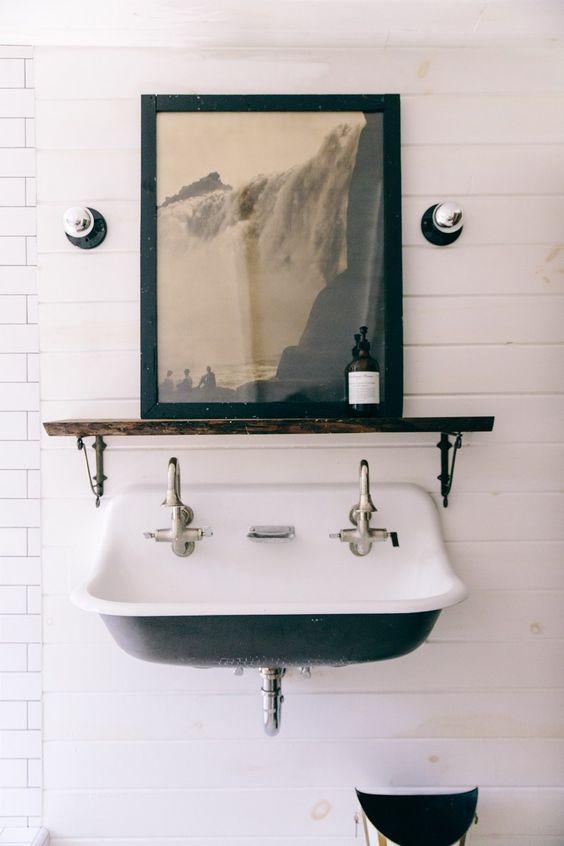 Inside Interior Designer Leanne Ford's Renovated Pennsylvania Schoolhouse, this vintage farm trough sink looks chic with modern art and minimal lighting. #LeanneFord #farmhousebath #vintagesink
